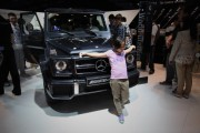 A Chinese girl poses beside a Mercedes-Benz Class G 63 AMG car during the 2012 Beijing International Automotive Exhibition at China International Exhibition Center on April 29, 2012 in Beijing, China.